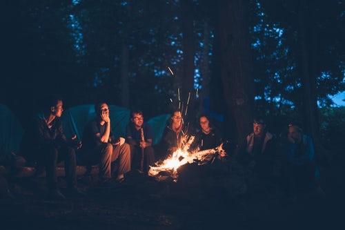 Lagerfeuer mit Menschen am Abend